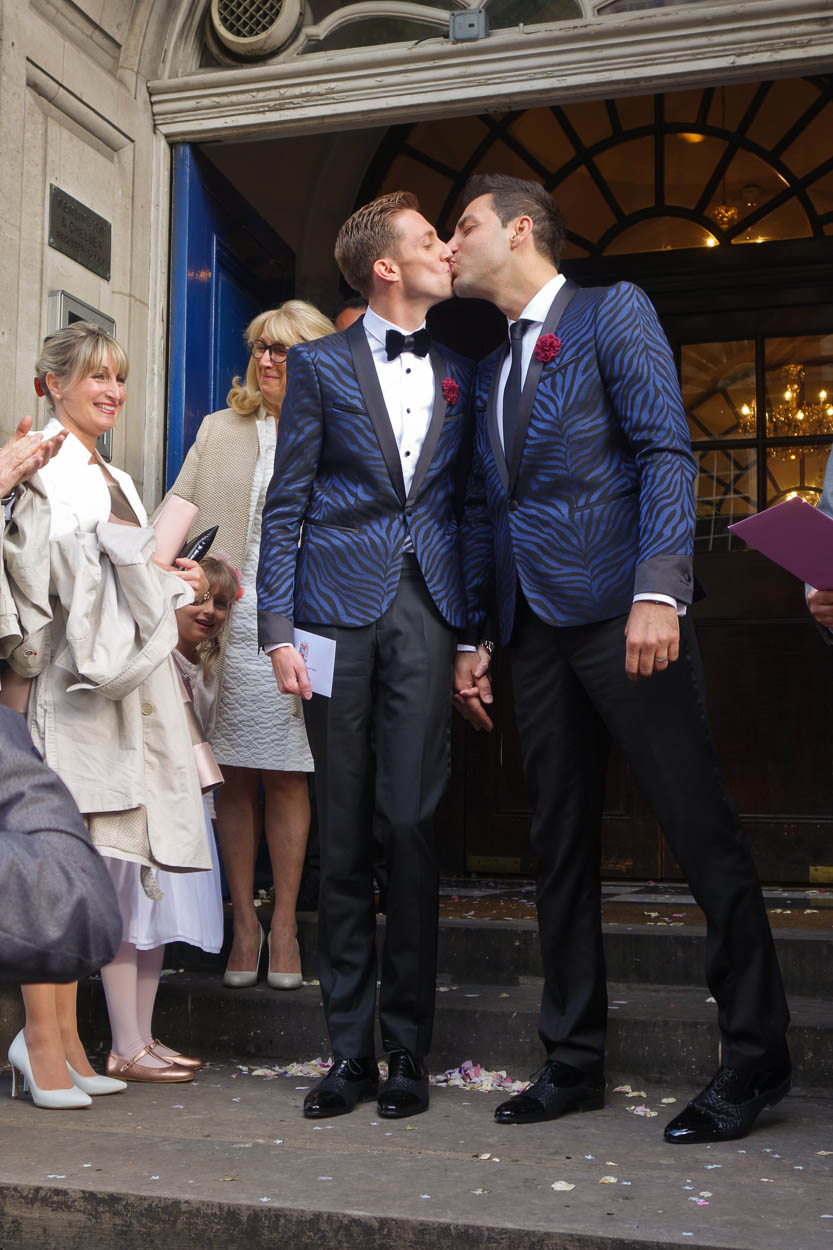 Antoine and Martin kiss on the steps of Chelsea Old Town Hall after their wedding ceremony