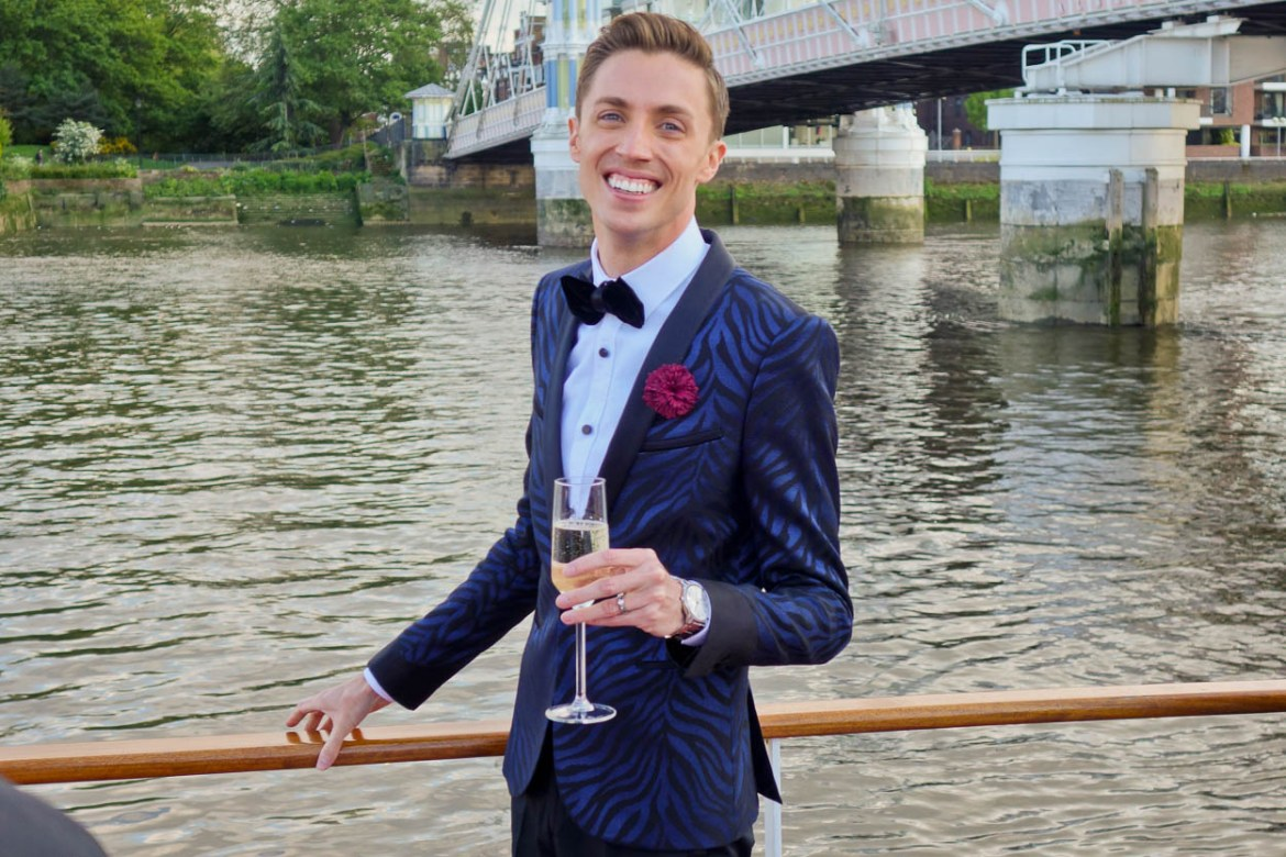 Antoine smiling with a glass of champagne aboard the MV Edwardian, London
