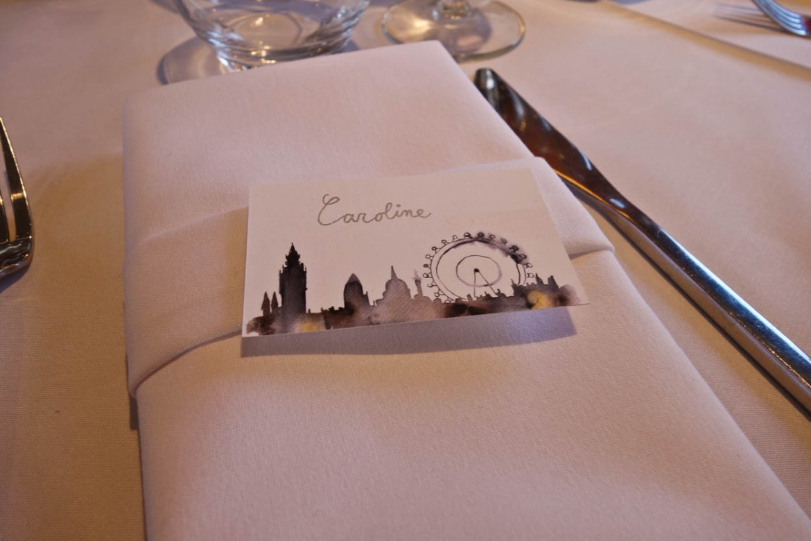 Handwritten wedding reception place card featuring the London skyline