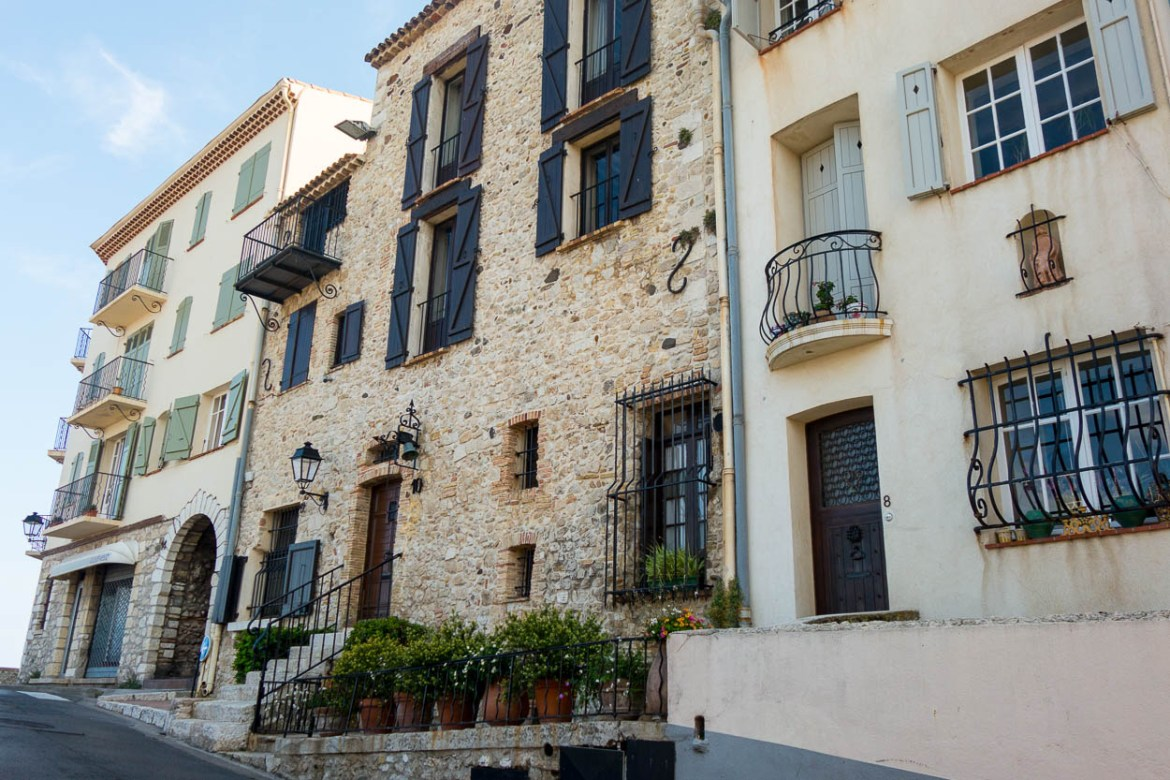 Pretty French houses with shutters and wrought iron balconies in Antibes