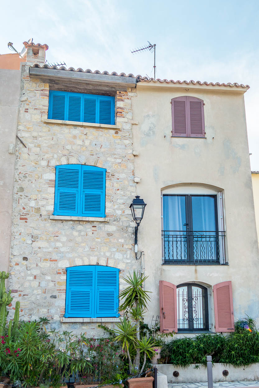 Blue and pink shutters on sea-front houses in old Antibes