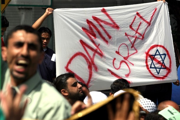 """Malaysian protesters from the Malaysian Islamic Party (PAS) hold banners and shout slogans during a rally against the recent Israeli military attacks on Gaza, outside the US embassy in Kuala Lumpur on December 30, 2008. Warplanes pounded Gaza for a fourth day as tanks stood by to join the """"all-out"""" war Israel vowed would wipe out Hamas, and the Palestinian death toll rose to at least 360. Israel made it clear on December 29 the offensive was just beginning, even as UN chief Ban Ki-moon urged world leaders to work urgently to end the """"unacceptable"""" violence. AFP PHOTO (Photo credit should read AFP/AFP/Getty Images)"""