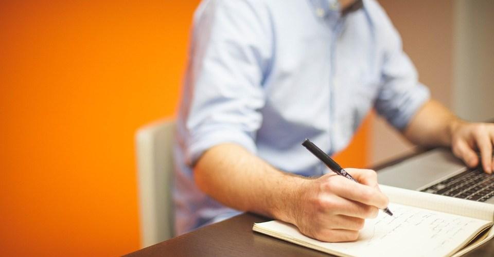 man sitting at desk writing resume