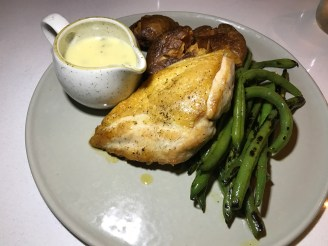 chicken with charred green beans, smashed red skin potatoes, and tarragon beurre blanc