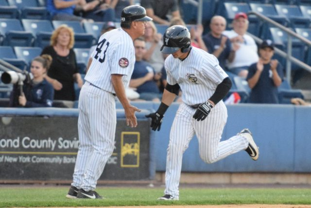 Dalton Blaser gives Staten Island Yankees manager Dave Bialas a five as he rounds third base on his way home. (Robert M. Pimpsner)