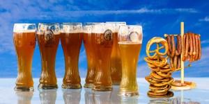 7 Pilsner glasses full of lager next to a stack of pretzels