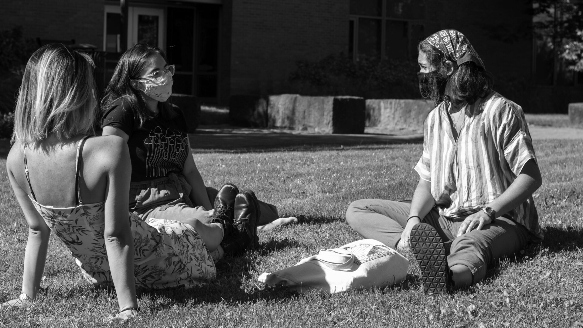 Students sit on the lawn wearing masks.