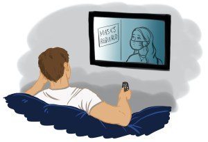A person sits on a couch watching the television.