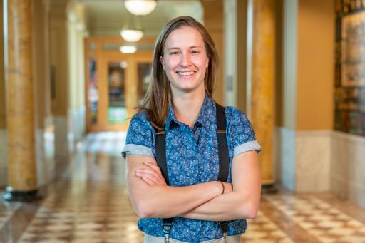 Seraphie Allen, smiling and wearing a button down shirt and suspenders, poses in front of a long hallway.
