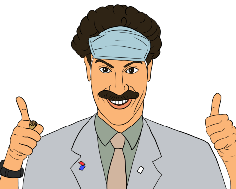 The character Borat grins and gives two thumbs up, wearing his face mask on his head.