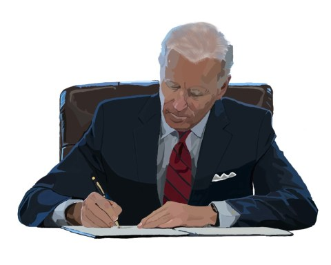 President Joe Biden signs an executive order at his desk in the Oval Office