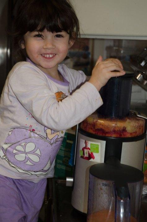 Isabelle hygger sig med juiceproduktionen - man kan godt blive lidt beskidt i køkkenet :-)