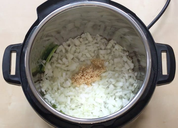 Onions, ginger and garlic added to instant pot to make red beans curry