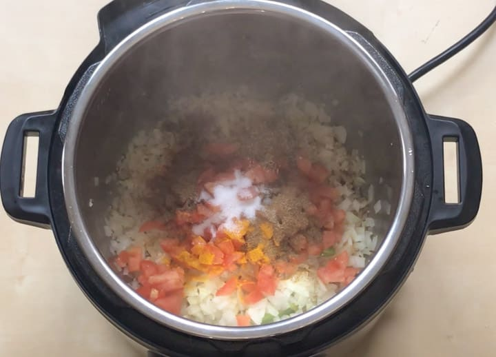 Add tomato and spices to instant pot for Rajma Masala