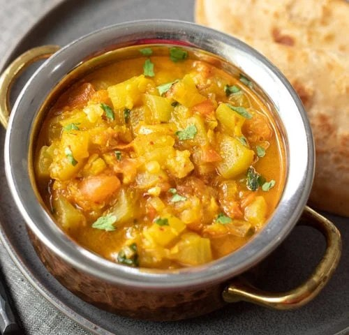 Bottle Gourd Curry (Lauki) in a bowl with roti and ghee