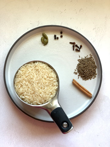 Basmati Rice and whole spices on a white plate