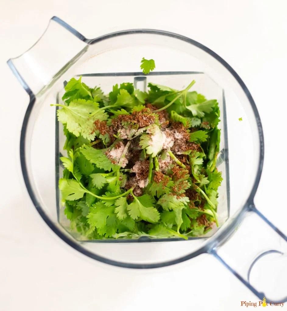 Ingredients such as cilantro cumin powder, salt in a Vitamix blender