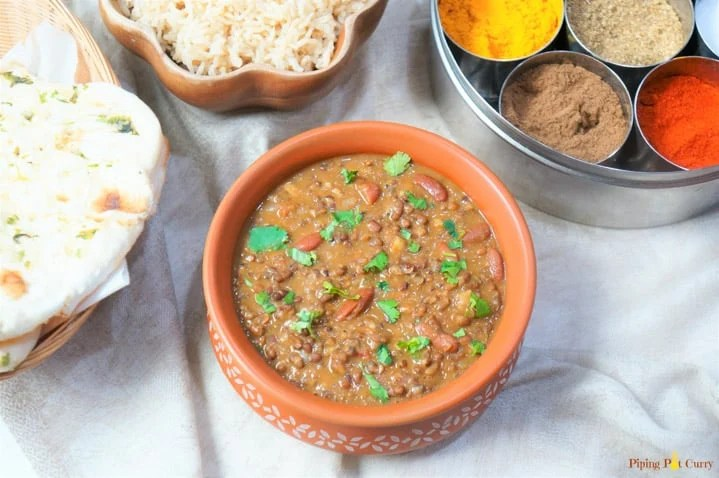 Dal Makhani made in the instant pot, served in a earthen pot with some brown rice and spices in the back