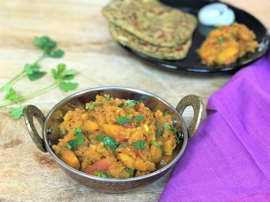 Instant Pot Pumpkin curry in a kadhai with cilantro for decoration. In the back, a plate with the pressure cooker pumpkin curry, parathas and onions.