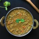 Green lentils in a bowl garnished with cilantro