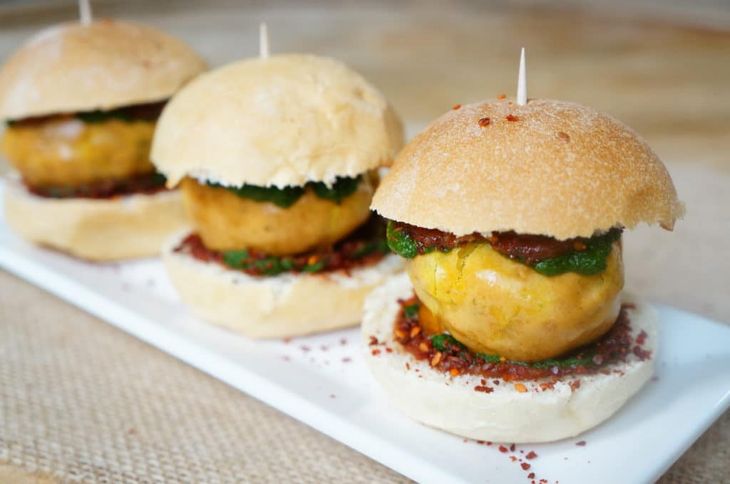 Potato Fritter Sliders, is a game day twist of the humble Mumbai street food, Vada Pav. A fried potato fritter is stuffed in between dinner rolls, along with sweet and spicy sauces or chutney