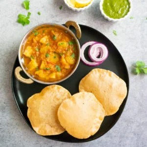 Potato Curry along with puffed bread (puri) and onions in a black plate