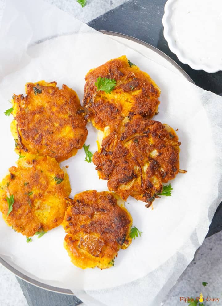 Vegan Chickpea Squash Fritters in a plate with yogurt dip on the side