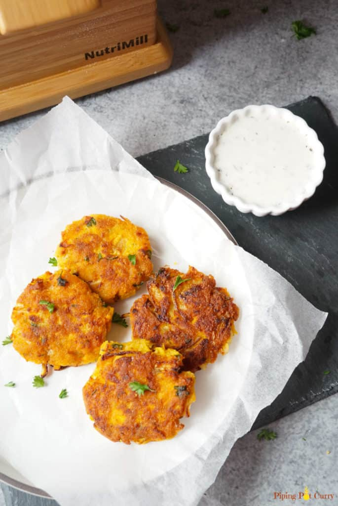 Vegan Chickpea Squash Fritters in a plate with yogurt dip on the side and Nutrimill Harvest in the back