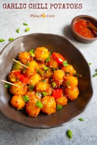 Flavorful and easy Garlic Chili Potatoes, made with steamed potatoes, garlic, chili sauce and honey, sprinkled with green onions and sesame seeds. Enjoy them as an appetizer or side! #chilipotatoes #garlicpotatoes #indochinese #chinese #vegan | pipingpotcurry.com