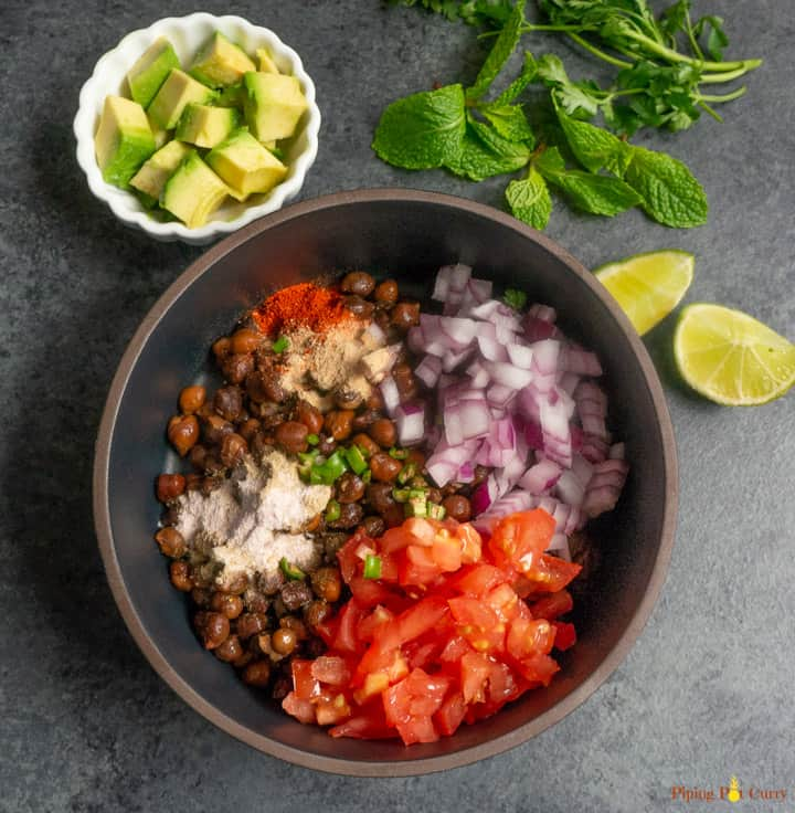 Kala Chana Chaat. Black Chickpea Salad - Start mixing the ingredients by adding to black chickpeas