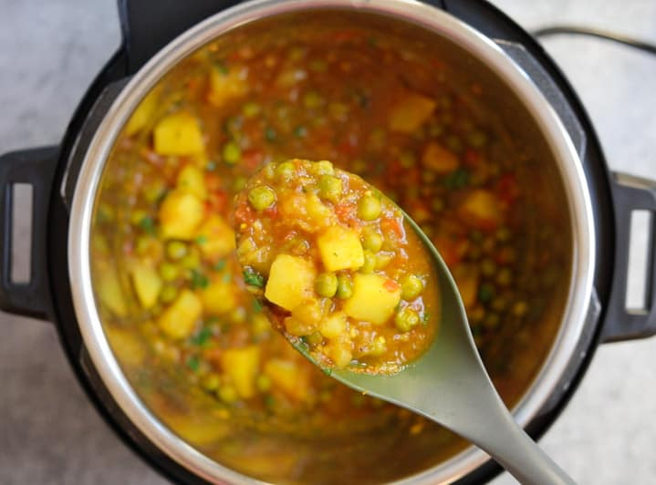 Aloo Matar in instant pot - perfectly cooked and shown in a ladle
