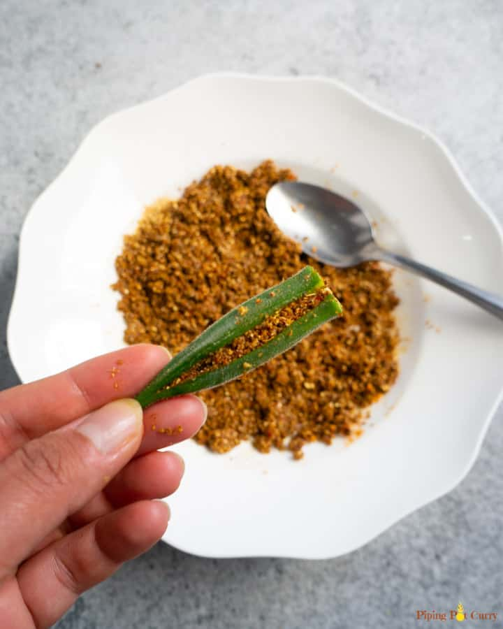 Okra stuffed with spices shown in hand with the spice mix in the back