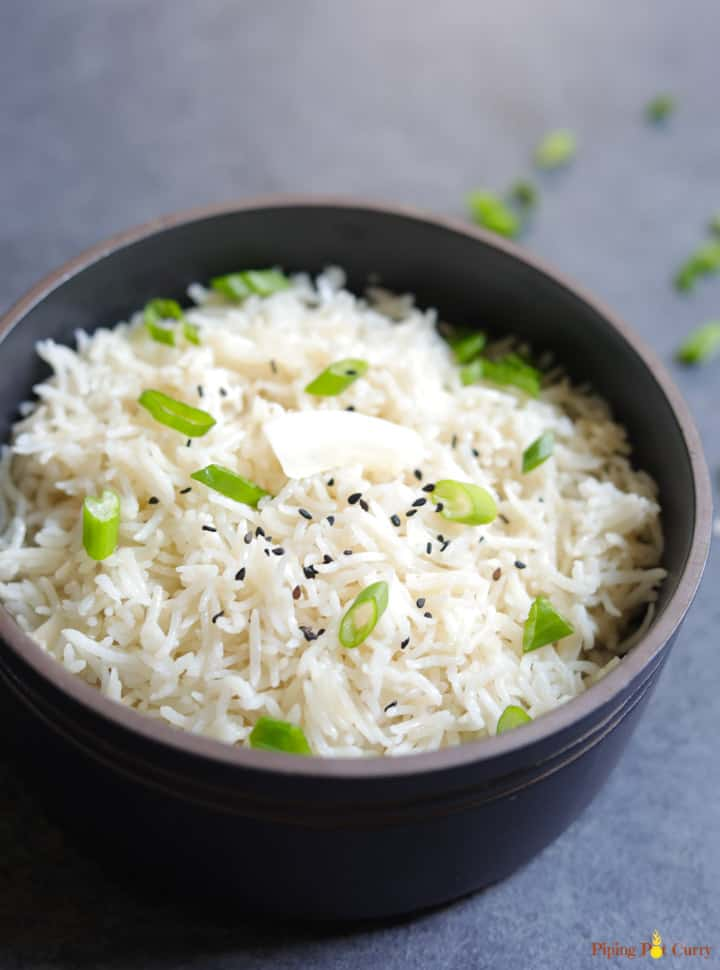 Coconut Rice cooked in pressure cooker topped with coconut flakes