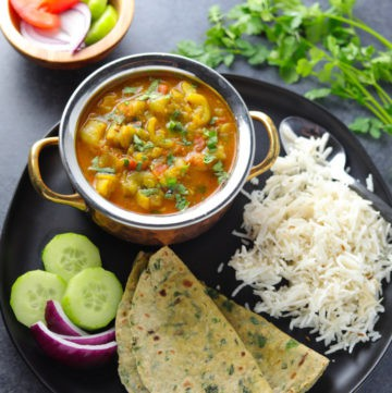 Ridge Gourd Curry or Turai ki subii served with roti, rice and salad in a plate
