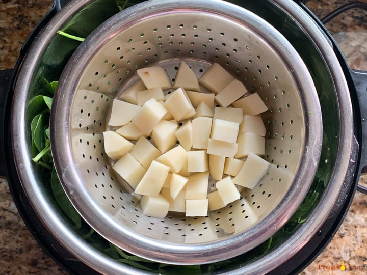 A steamer basket with potatoes placed on top of spinach in the instant pot to be cooked to make saag aloo