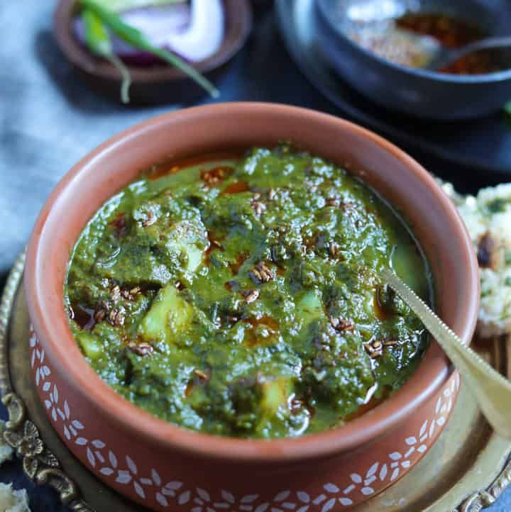 Saag Aloo made in the instant pot served in a earthen bowl with the tempering in the back and naan on the side.