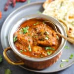 Chicken Vindaloo served in a bowl along with naan bread.