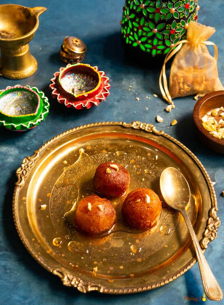 Gulab Jamun served on a plate with some festive decorations.