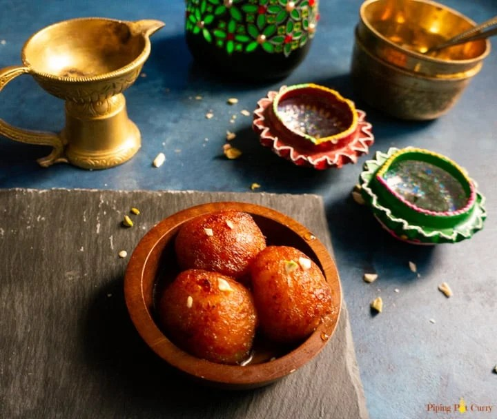 Gulab Jamun served in a small wooden bowl with a spoon.