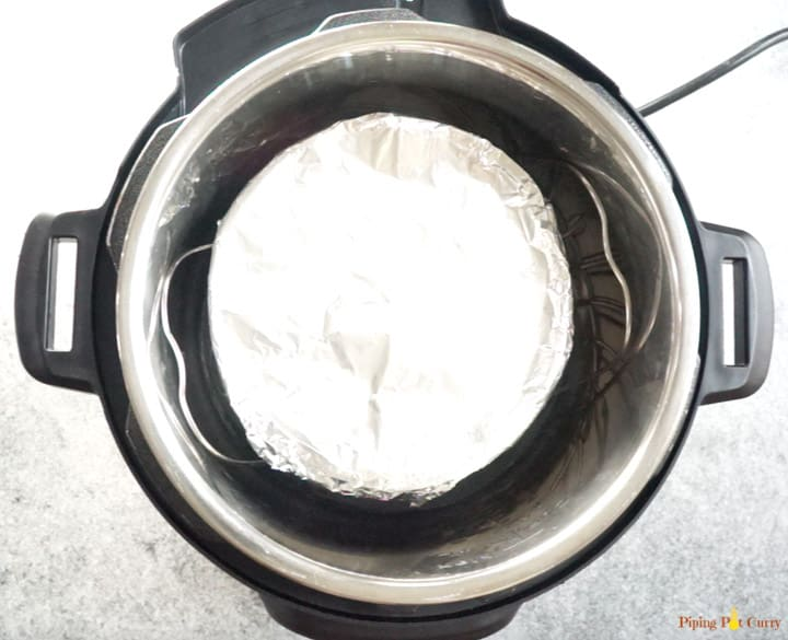 Cake pan filled with brownie batter and covered with foil placed on a trivet to make instant pot brownies