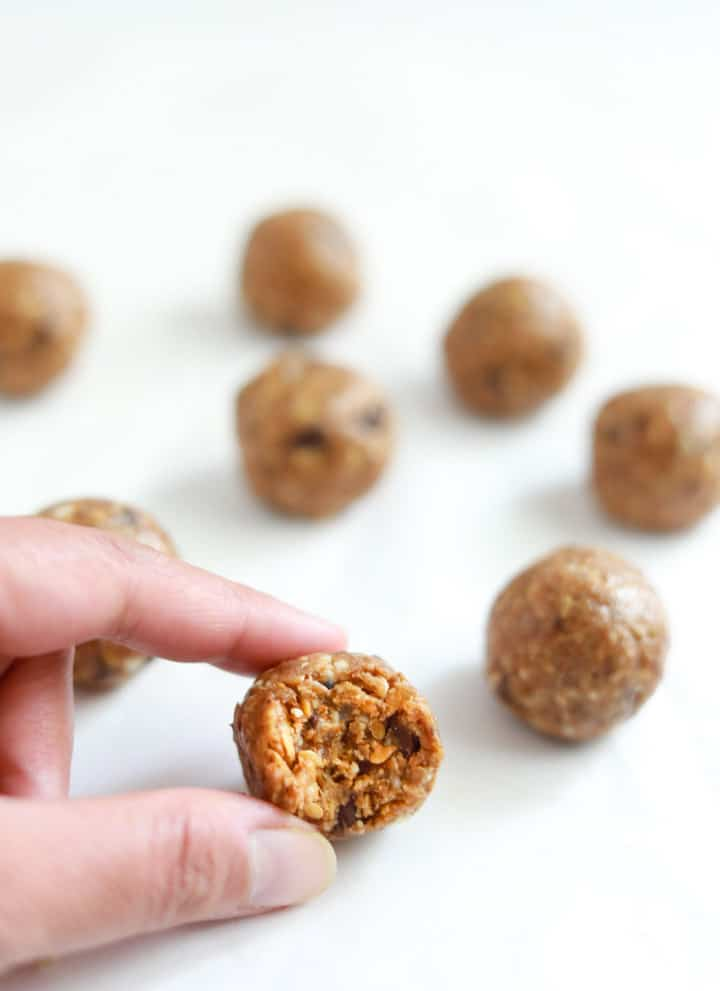 A half eaten Almond Butter Energy Ball closeup, with many more almond balls in the back