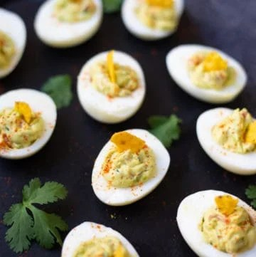 Guacamole Deviled Eggs on a black base with cilantro spread around