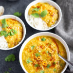 Red Lentils served in 3 bowls over rice and topped with cilantro