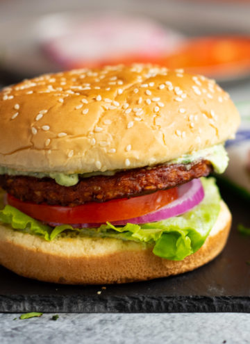 Burger with lettuce, tomato, onion and dressing flowing.