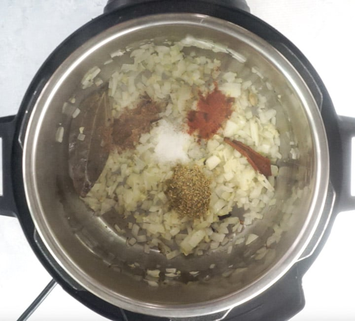 Onions along with spices in an electric pressure cooker