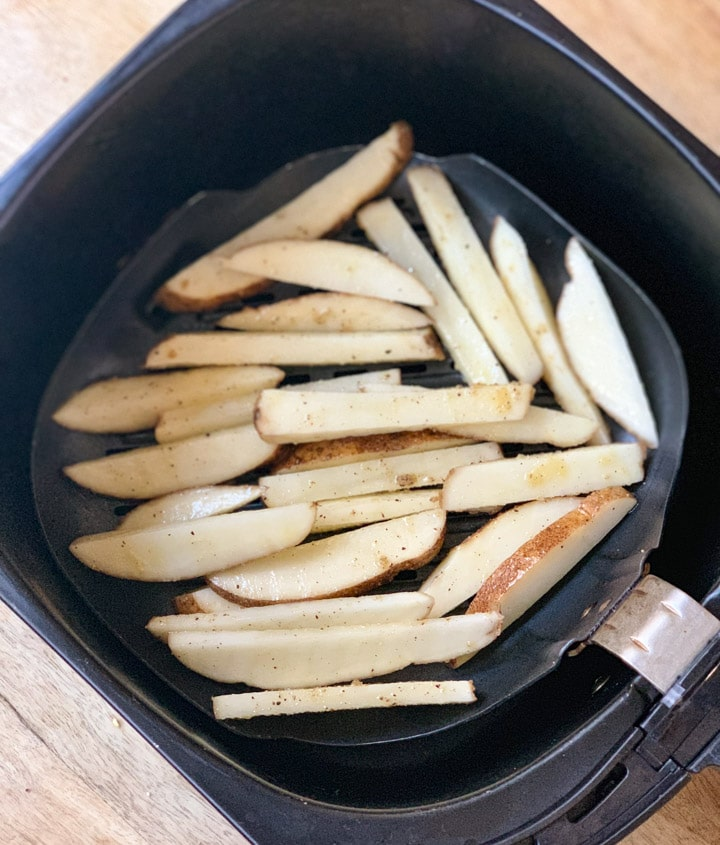 Sliced seasoned potatoes in the air fryer basket