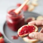 Closeup of a sliced bread topped with strawberry jam