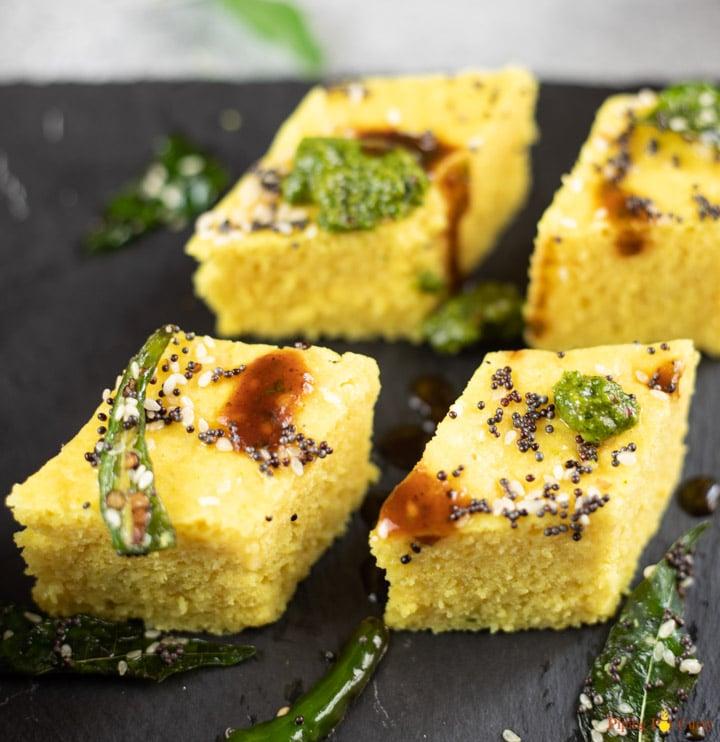 Four pieces of yellow Khaman dhokla on a black platter