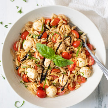 Caprese Orzo Pasta Salad in a white bowl garnished with balsamic and basil