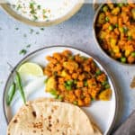 Aloo Gajar Matar (Potato, Carrots & Peas) along with roti (indian flatbread) in a white plate along with yogurt raita on the side.